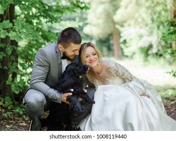 Bride and groom play with fluffy dogs standing in the forest
