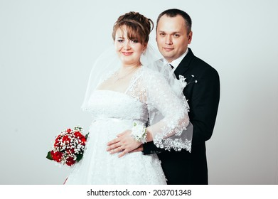 Bride and groom portrait in studio. Cheerful cute married couple posing on white background