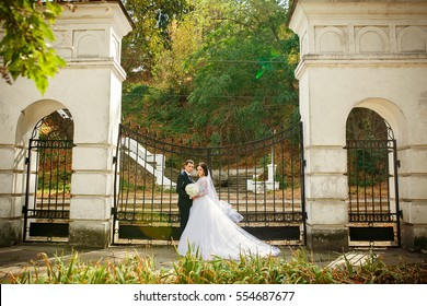 Bride and groom posing in summer park outdoors with architecture.