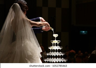 The bride and groom pour the champagne into the glass tower.
