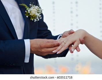 The bride and groom put on wedding rings. Wedding ceremony in the open air