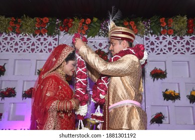 Bride and groom putting garland as a ceremonial proceeding as per Hindu Marriage Rituals and posing for the photograph. The Garland and is made of roses and white flower buds