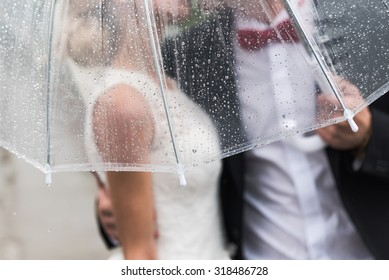 the bride and groom in the rain are covered with a transparent umbrella, rain drops
