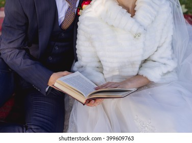 The bride and groom read a book in the park