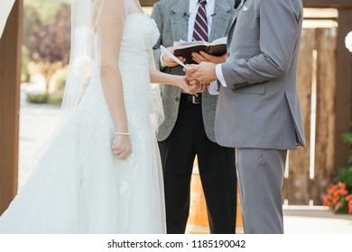 Bride and groom reading wedding vows during ceremony.