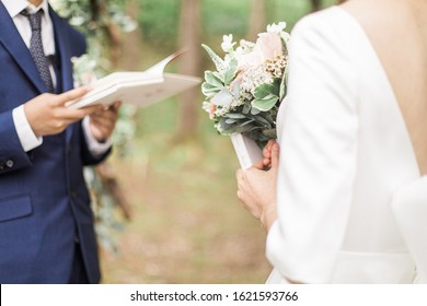 Bride and groom reading wedding vows from paper at wedding ceremony in nature.