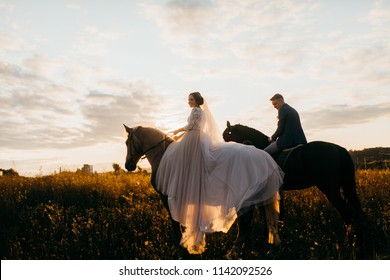 Bride and groom ride on horses. Sunset.