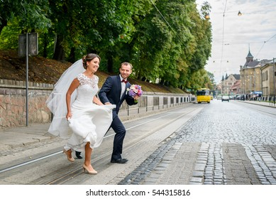 Bride and groom run across the street somewhere in old city