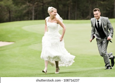 bride and groom running on the green grass