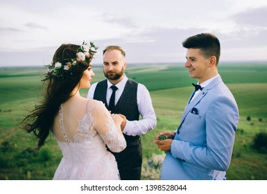 Bride and groom saying their vows outdoors in front of the man of honor