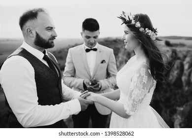 Bride and groom saying their vows in front of the man of honor in black and white
