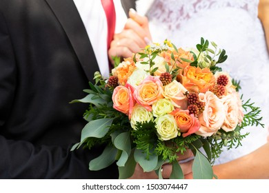 Bride and groom show off their beautiful bouquet of flowers