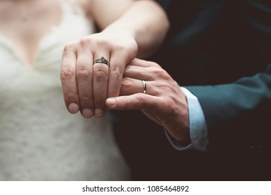 Bride and groom showing his rings after the wedding.