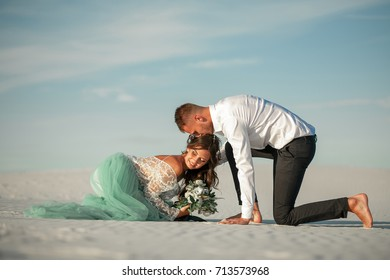 Bride and groom sit barefoot on sand in desert, hug and smile. They sit on background of white sand and blue sky.