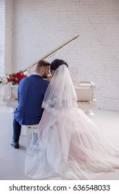 The bride and groom sit next to the piano