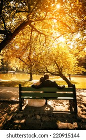 Bride and groom sit on bench in park in sunset light