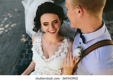 Bride and groom sit on the bench and having fun