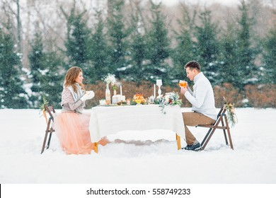 The bride and groom sit at a table. Winter wedding.