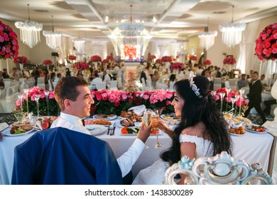 The bride and groom sit at the wedding table, clink glasses with smiles and look at each other. Against the backdrop of a huge banquet hall.