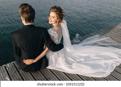 Bride and groom sitting by the lake