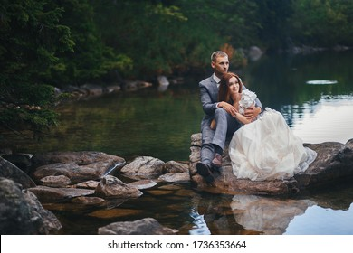The bride and groom are sitting on a large stone in the lake. Wedding concept. Copy space