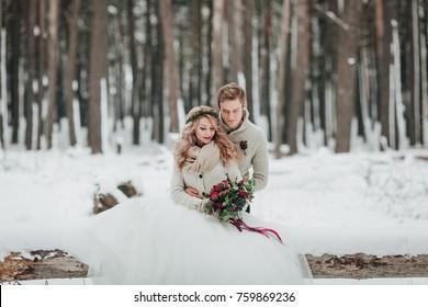 Braut und Bräutigam sitzen im Winterwald auf dem Baumstamm. Nahaufnahme. Winterhochzeit.