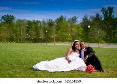 Bride and groom sitting together in a field near the wedding ceremony.