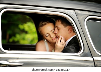 Bride and groom sitting in the vintage car and going for a kiss. Romantic moment.