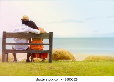 A bride and groom sitting wooden bench on the beach
