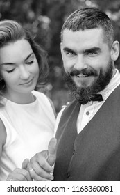 Bride and groom smiling with wedding rings black and white