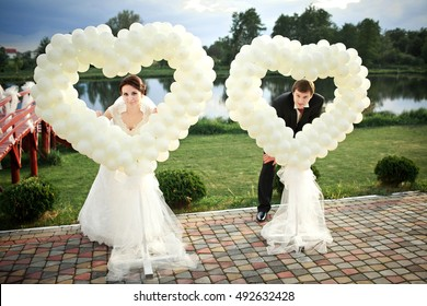 Bride and groom stand behind decorative hearts made of white balloons