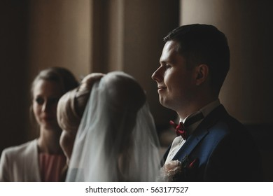 The bride and groom stand in the church