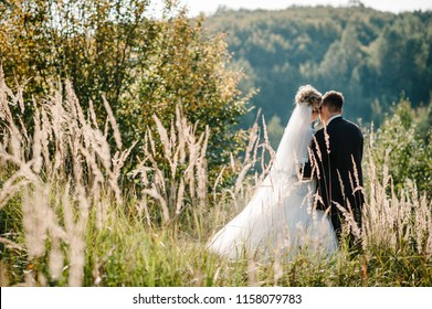 The bride and groom stand in the field after the wedding ceremony.