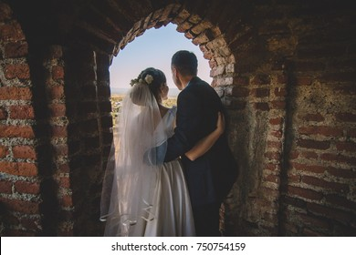 The bride and groom stand on an ancient fortress
