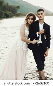 Bride and groom stand in the waters of mountain river