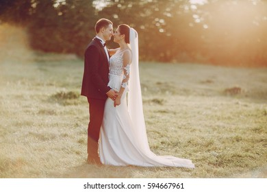 bride and groom standing against a background of green trees and the sun shines on them