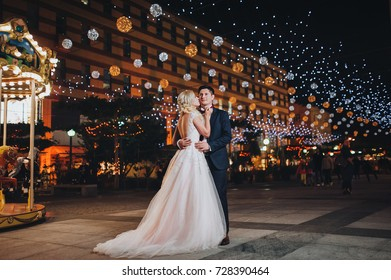 The bride and groom are standing in the background of a night cityscape.