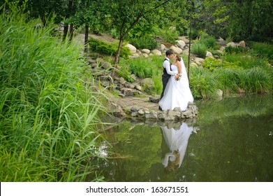 bride and groom standing in a beautiful green park near the lake