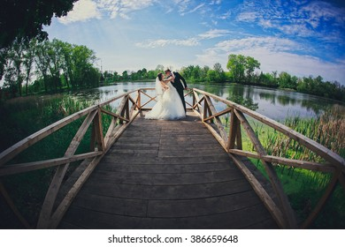 bride and groom are standing at the edge of the bridge over a beautiful lake, happy wedding photography