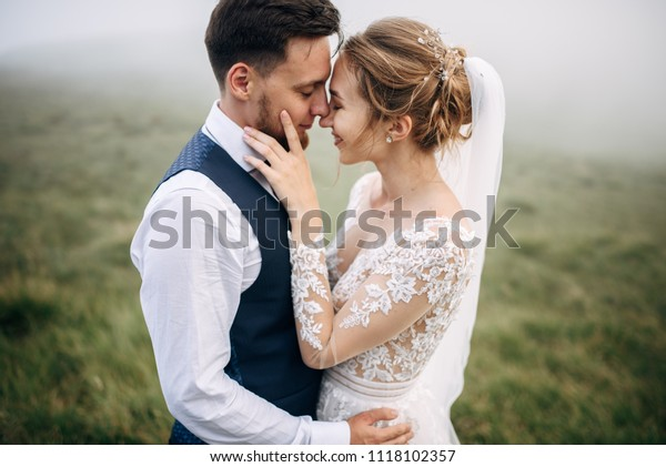 Bride and groom are standing face to face with the green hills on background
