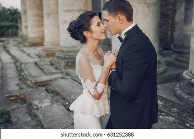 bride and groom standing near large columns and stairs