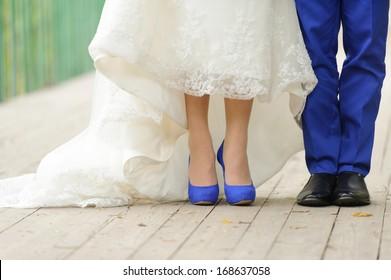 bride and groom standing on bridge in park