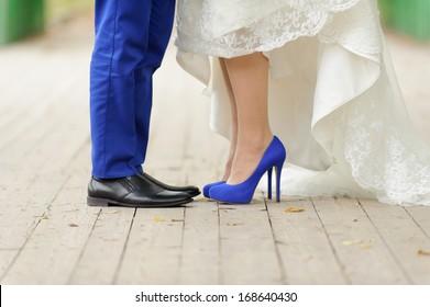 bride and groom standing on wooden bridge in park
