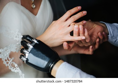 The bride and groom standing together in the bright room during the marriage ceremony. They are putting on each other's rings. Man has bionic prosthetic arm.
