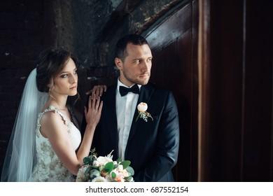 Bride and groom stands before an old wooden door