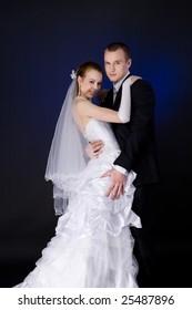 Bride and groom studio portrait over blue background
