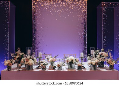 Bride and groom table setting and flower decoration. Presidium of the newlyweds on a blue background. Cutlery on the table. Floral decorations in the banquet hall.