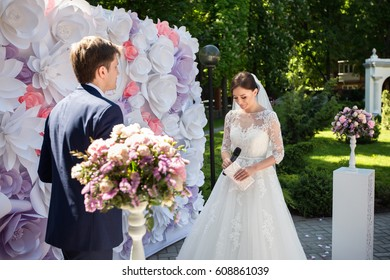 Bride and groom take vows at wedding ceremony near beautiful wedding arch of paper flowers