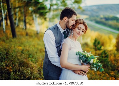 the bride and groom with their eyes closed stand in an embrace against the autumn nature