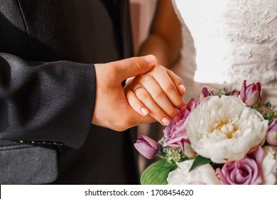 A bride and groom with their hands on top of the flowers, showing off their rings. Horizontal photo.